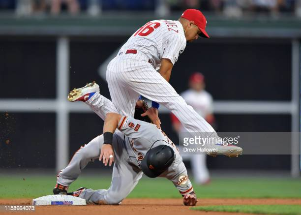 Cesar Hernandez of the Philadelphia Phillies jumps over Mike Yastrzemski of the San Francisco Giants after putting him out at second base after in...