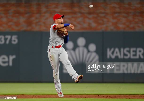 Cesar Hernandez of the Philadelphia Phillies makes a throwing error as he attempts to field a grounder by Nick Markakis of the Atlanta Braves in the...