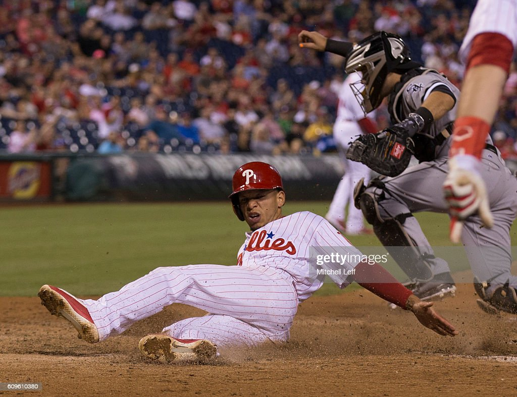 Cesar Hernandez #16 of the Philadelphia Phillies slides past Alex Avila #31 of the Chicago White Sox to score a run in the bottom of the sixth inning at Citizens Bank Park on September 21, 2016 in Philadelphia, Pennsylvania. The Phillies defeated the White Sox 8-3.