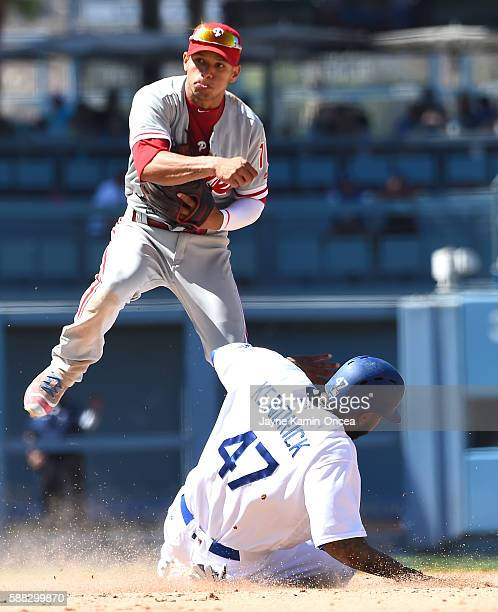 Cesar Hernandez of the Philadelphia Phillies throws to first as Howie Kendrick of the Los Angeles Dodgers is out at second as he breaks up a double...
