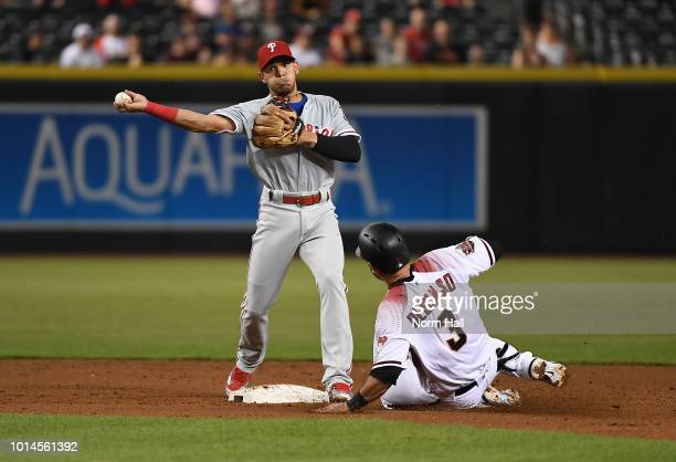 Cesar Hernandez of the Philadelphia Phillies turns a double play as Daniel Descalso of the Arizona Diamondbacks slides into second base during the...