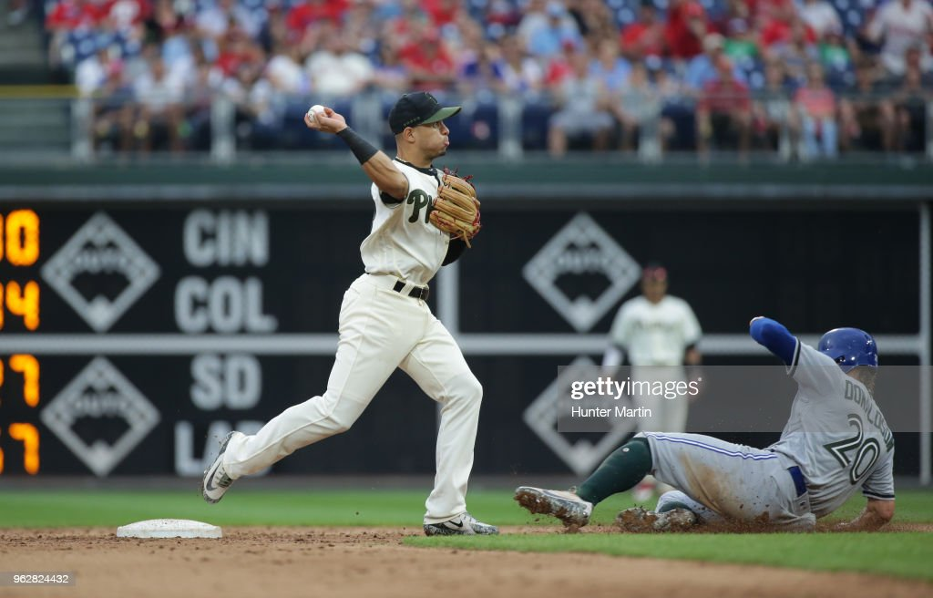 Cesar Hernandez #16 of the Philadelphia Phillies turns a double play in the ninth inning as Josh Donaldson #20 of the Toronto Blue Jays slides under the throw during a game at Citizens Bank Park on May 26, 2018 in Philadelphia, Pennsylvania. The Phillies won 2-1.