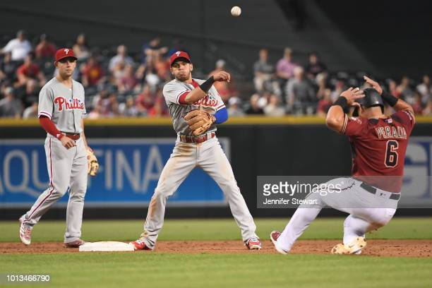 Cesar Hernandez of the Philadelphia Phillies turns the double play over David Peralta of the Arizona Diamondbacks during the MLB game at Chase Field...