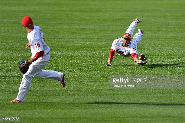 Cesar Hernandez watches as Ben Revere of the Philadelphia Phillies dives unsuccessfully for the ball hit by Scooter Gennett of the Milwaukee Brewers...