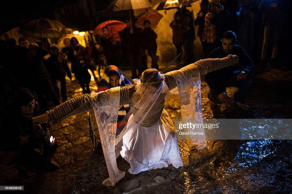 Cesar Higuero Martin, aged 25, prays at one station of the way of the cross or 'Via Crucis' during the procession of the 'Empalaos' on March 29, 2013 in Valverde de la Vera, Spain. Empalaos make the steps of the 'Via Crucis', marking the Stations of the Cross, during the night of Maundy Thursday while bound by rope to a crucifix as an act of penance and to honour a promise made to the Empalaos Brotherhood and the Christ of Vera Cruz, in the town of Valverde de la Vera. The process of dressing the Empalao in the traditional costume is taken with great care, with the family and dressers paying attention to ensure that no harm is caused to the penitent and that they are aided in their recovery, including being massaged and rubbed with rosemary alcohol. Many Spanish towns and villages retain such rites and religious traditions, many passed down from medieval times, across the Easter weekend.