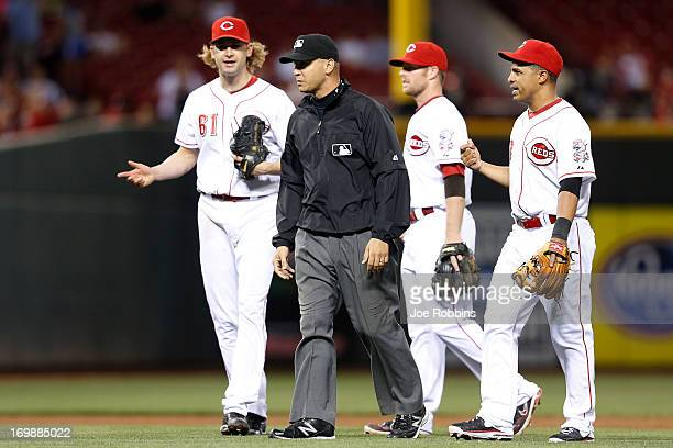 Cesar Izturis and Bronson Arroyo of the Cincinnati Reds question a call by third base umpire Vic Carapazza during the game against the Colorado...