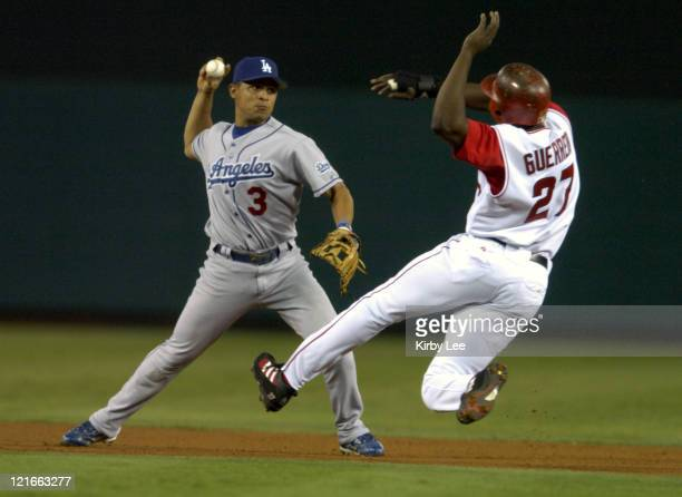 Cesar Izturis of the Los Angeles Dodgers avoids a sliding Vladimir Guerrero of the Anaheim Angels for a force out at second base during fourth inning...