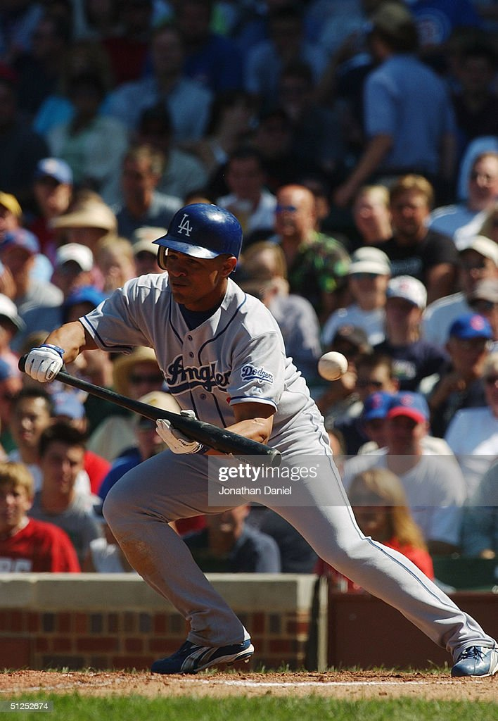 Cesar Izturis #3 of the Los Angeles Dodgers bunts during a game against the Chicago Cubs on August 15, 2004 at Wrigley Field in Chicago, Illinois. The Dodgers defeated the Cubs 8-5.