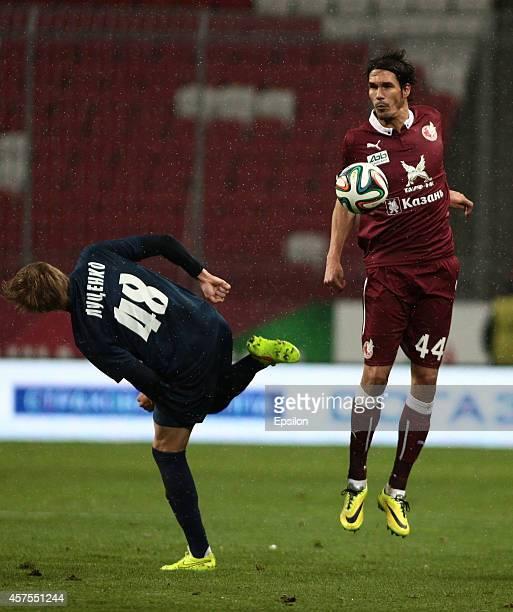 Cesar Navas of FC Rubin Kazan is challenged by Yevgeni Lutsenko of FC Mordovia Saransk during the Russian Football League Championship match between...
