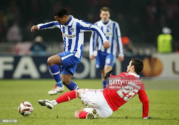 Cesar Peixoto of Lisbon battles for the ball with Raffael of Berlin during the UEFA Europa League knock-out round, first leg match between Hertha BSC...