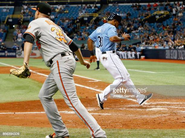 Cesar Puello of the Tampa Bay Rays touches home in the bottom of the eighth inning for the team's third run as Brad Brach of the Baltimore Orioles...