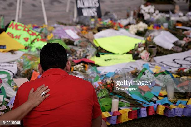 Cesar Rodriguez, friend of Amanda Alvear who was killed in the shooting, is comforted by Lisa Dominguez at a makeshift memorial at the Dr. Phillips...