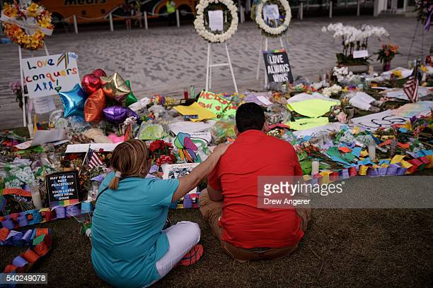 Cesar Rodriguez , friend of Amanda Alvear who was killed in the shooting, is comforted by Lisa Dominguez at a makeshift memorial at the Dr. Phillips...