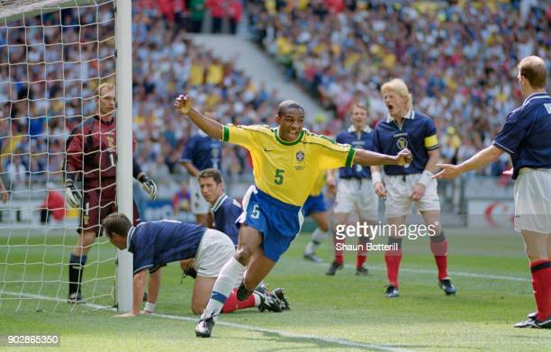 Cesar Sampaio of Brazil celebrates scoring the opening goal of the World Cup as Scotland captain Colin Hendry reacts during the group A game against...