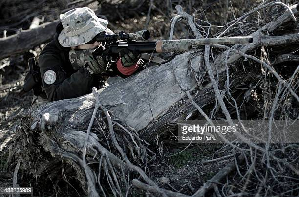 Cesar Tuda from spanish airsoft team Condenados provides sniper cover during the assault on an enemy position during a simulation of combat in a game...