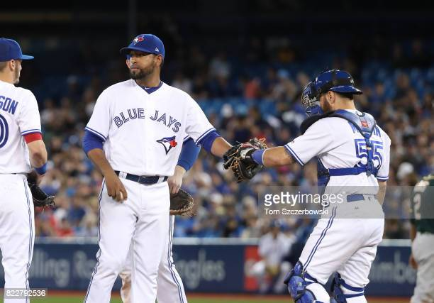 Cesar Valdez of the Toronto Blue Jays is congratulated by Russell Martin as he exits the game in the seventh inning during MLB game action against...