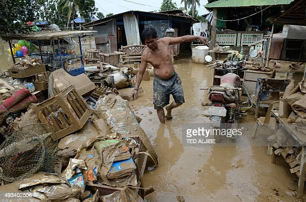 Cesar Veloso the father of Jane Veloso on death row at an Indonesian prison walks amongst mudfilled belongings after heavy rains brought about by...