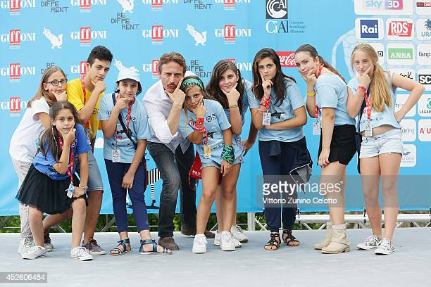 Cesare Bocci poses with children as he attends the Giffoni Film Festival photocall on July 24 2014 in Giffoni Valle Piana Italy