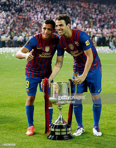 Cesc Fabregas and Alexis Sanchez pose with the trophy after their victory in the Copa del Rey Final match between Athletic Bilbao and Barcelona at...