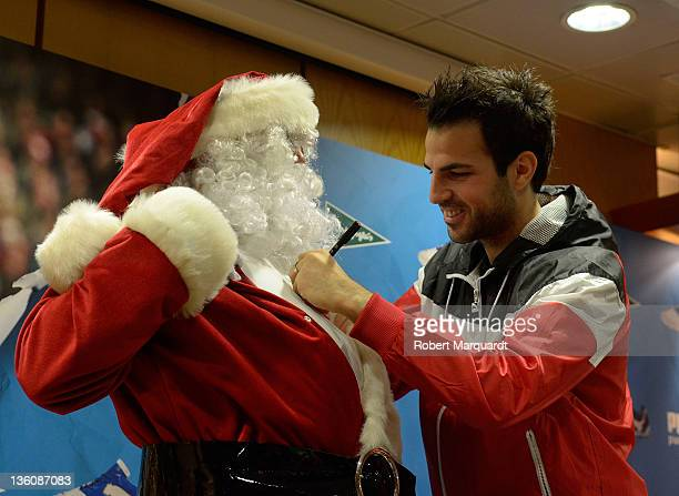 Cesc Fabregas autographs Santa Claus chest during a press presentation of the new Puma PowerCat 112 shoe at the Corte Ingles store on December 23...