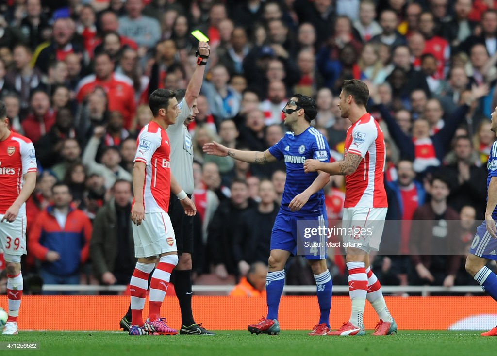 Cesc Fabregas is shown a yellow card by referee Michael Olivier during the Barclays Premier League match between Arsenal and Chelsea at Emirates Stadium on April 26, 2015 in London, England.