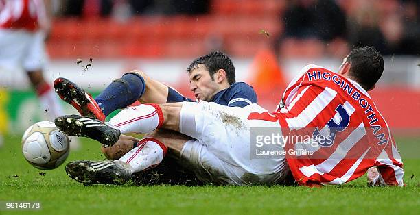 Cesc Fabregas of Arsenal battles with Danny Higginbotham of Stoke during the FA Cup sponsored by EON Fourth Round match between Stoke City and...