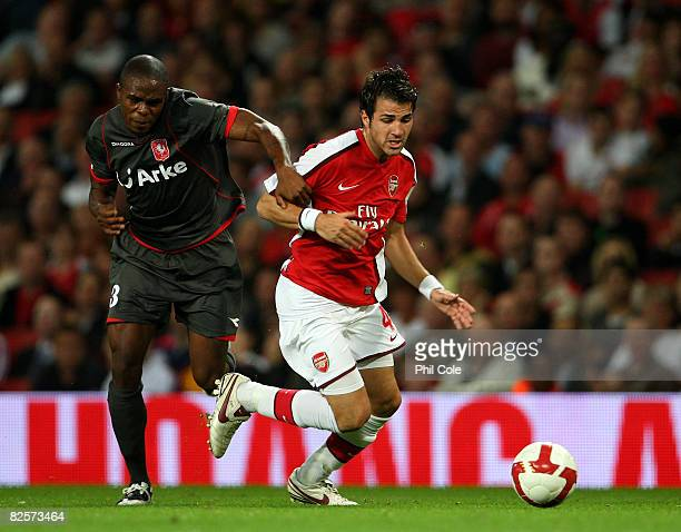 Cesc Fabregas of Arsenal is held on to by Edson Braafheid of FC Twente during the UEFA Champions League third qualifying round, second leg match...