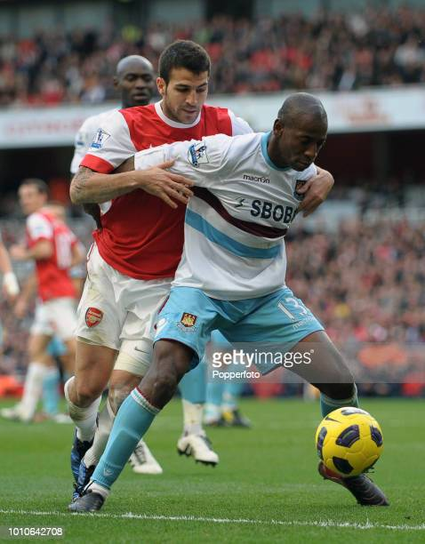 Cesc Fabregas of Arsenal tangles with Luis Boa Morte of West Ham United during the Barclays Premier League match between Arsenal and West Ham United...