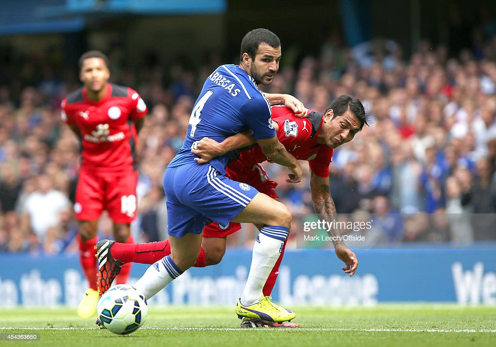 Cesc Fabregas (L) of Chelsea and Leonardo Ulloa of Leicester in a tussle for the ball during the Barclays Premier League match between Chelsea and Leicester City at Stamford Bridge on August 23, 2014 in London, England.
