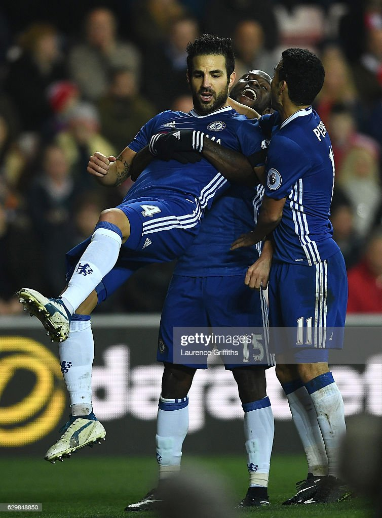 Cesc Fabregas (L) of Chelsea celebrates scoring his sides first goal with his Chelsea team mates Victor Moses (C) and Pedro (R) during the Premier League match between Sunderland and Chelsea at Stadium of Light on December 14, 2016 in Sunderland, England.
