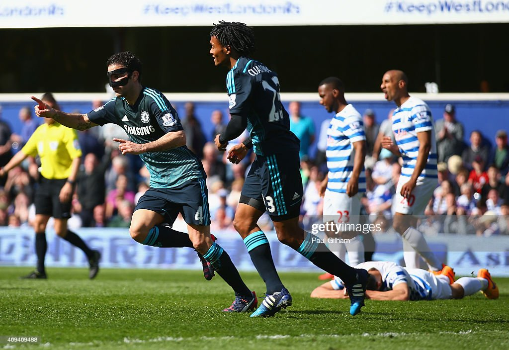 Cesc Fabregas of Chelsea celebrates scoring the opening goal with Juan Cuadrado of Chelsea during the Barclays Premier League match between Queens Park Rangers and Chelsea at Loftus Road on April 12, 2015 in London, England.