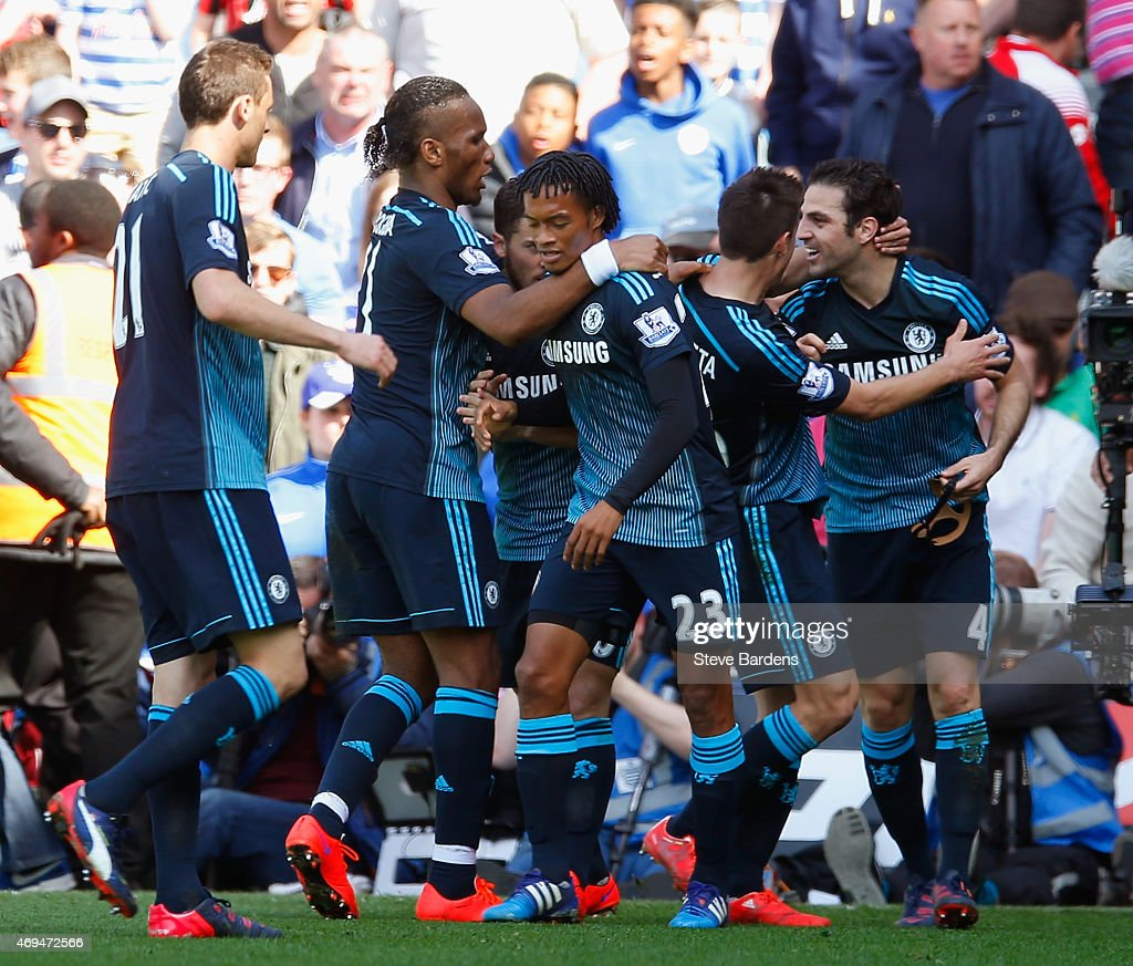 Cesc Fabregas of Chelsea celebrates scoring the opening goal with team mates during the Barclays Premier League match between Queens Park Rangers and Chelsea at Loftus Road on April 12, 2015 in London, England.