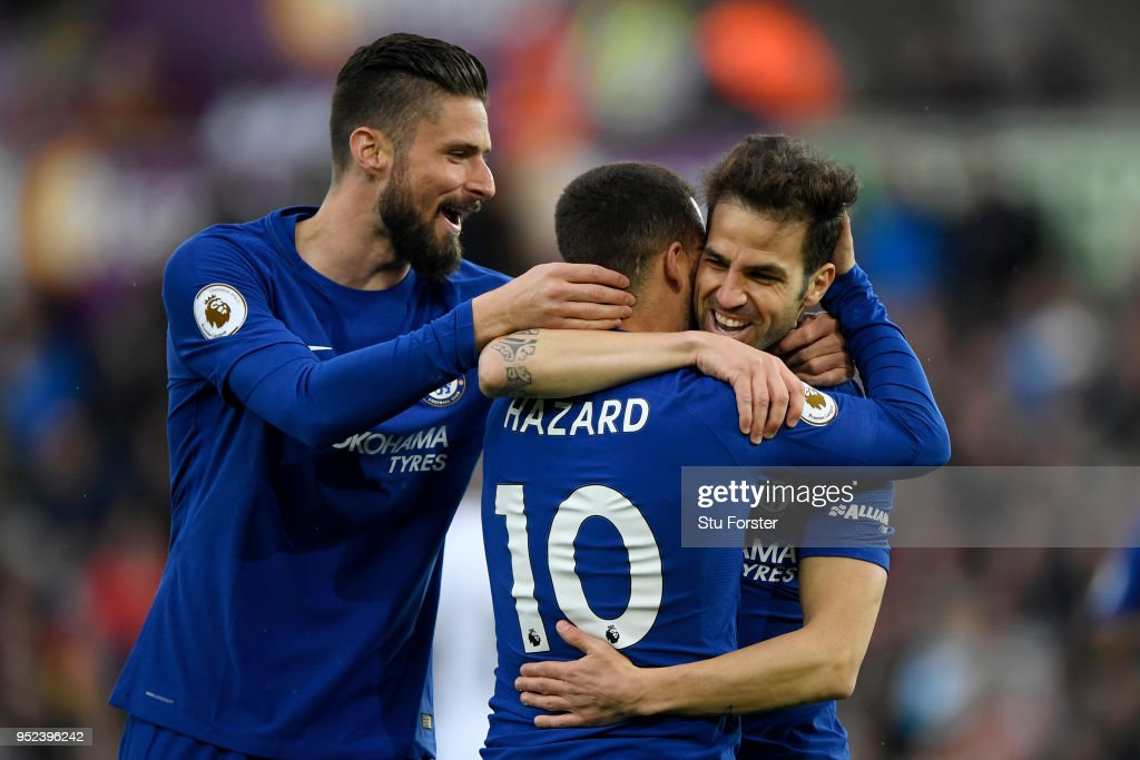 Cesc Fabregas of Chelsea celebrates with teammates Olivier Giroud and Eden Hazard after scoring his sides first goal during the Premier League match between Swansea City and Chelsea at Liberty Stadium on April 28, 2018 in Swansea, Wales.