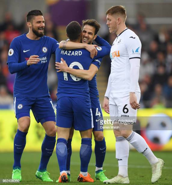 Cesc Fabregas of Chelsea celebrates with teammates Olivier Giroud and Eden Hazard after scoring his sides first goal during the Premier League match...
