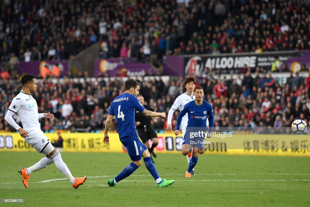 Cesc Fabregas of Chelsea scores his sides first goal during the Premier League match between Swansea City and Chelsea at Liberty Stadium on April 28, 2018 in Swansea, Wales.