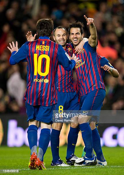 Cesc Fabregas of FC Barcelona celebrates with teammates Andres Iniesta and Lionel Messi after scoring the opening goal during the La Liga match...