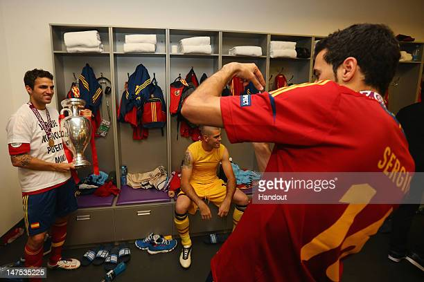 Cesc Fabregas of Spain poses in the dressing room with the trophy following the UEFA EURO 2012 final match between Spain and Italy at the Olympic...