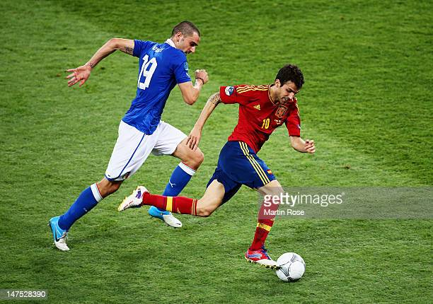Cesc Fabregas of Spain runs with the ball past Leonardo Bonucci of Italy during the UEFA EURO 2012 final match between Spain and Italy at the Olympic...