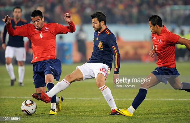 Cesc Fabregas of Spain tries to protect the ball from Mauricio Isla and Alexis Sanchez of Chile during the 2010 FIFA World Cup South Africa Group H...