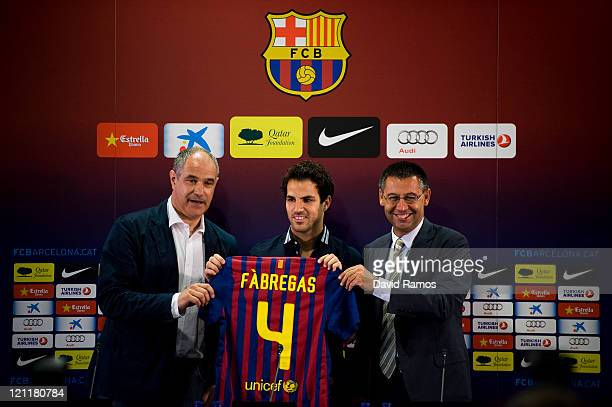 Cesc Fabregas shows his new tshirt surrounded by the Sport director Andoni Zubizarreta and the FC Barcelona CEO Josep Maria Bartomeu during his...