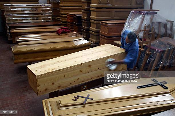 A worker polishes a Wojtyla model cypres coffin in a firm in the central Italian town of Cesena 05 July 2005 The coffinmaker has been advertising in...