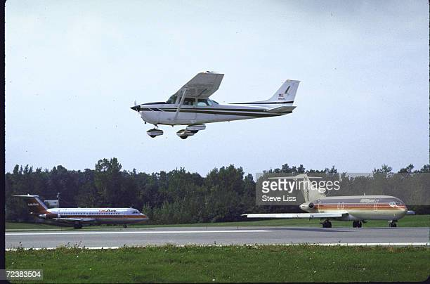 Cessna plane is landing while PEOPLE EXPRESS US AIR jets wait for clearance