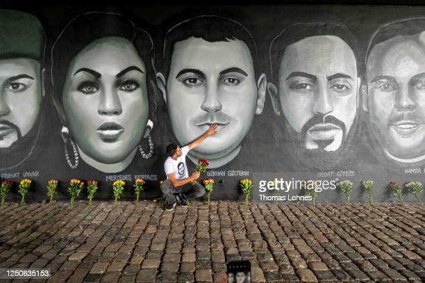 Cetin Gueltekin , the brother of Goekhan Gueltekin kneels with some flowers and touches the face of Goekhan in front of a 27 meter long street art...