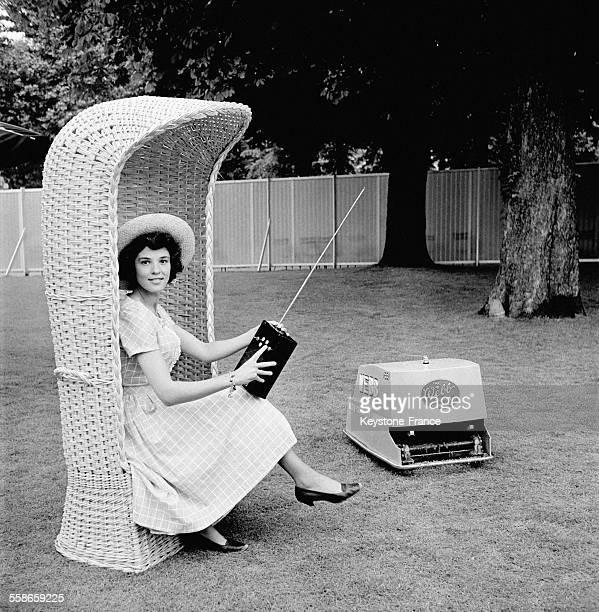 Cette jeune femme présente la nouvelle tondeuse à gazon télécommandée en France le 24 mai 1960