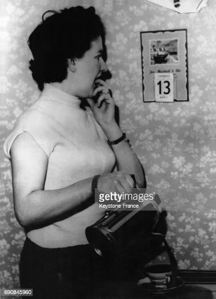 Cette jeune ménagère regarde le calendrier mural où est indiqué la date du Vendredi 13 tout en versant son café en France le 13 avril 1964