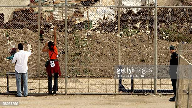 Two persons put flowers in the Spanish border fence with Morocco in Ceuta 05 November 2005 during the demonstration of solidarity with the immigrants...