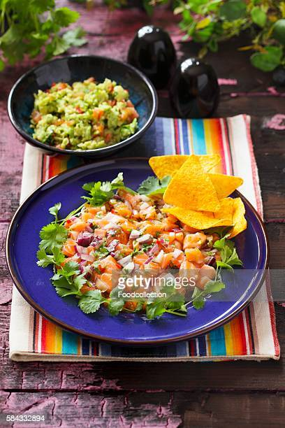 ceviche as a main course on a blue plate with coriander and tortilla chips and a bowl of guacamole in the background - ceviche fotografías e imágenes de stock