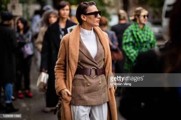 Ceylan Atinc wearing caramel colored wool coat belted blazer jacket white pants Dior shoes sunglasses seen during MercedesBenz Tbilisi Fashion Week...