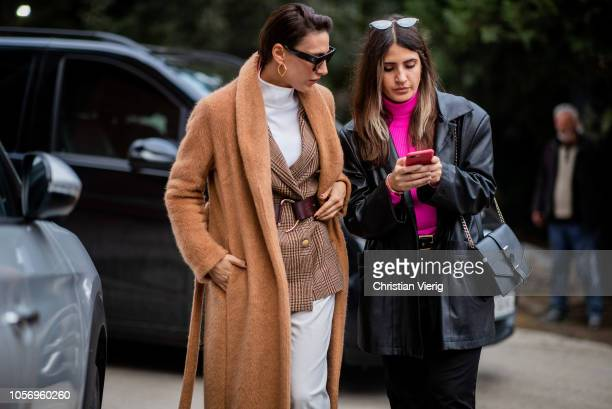 Ceylan Atinc wearing caramel colored wool coat belted blazer jacket white pants sunglasses and Selenm Ecoglu wearing black leather coat seen during...