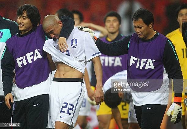 Cha DuRi of South Korea is consoled by team mate Ahn JungHwan and coaching staff after being knocked out of the competition during the 2010 FIFA...